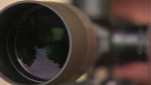 a man with one eye nearly closed looks through the sight of a rifle. - fadenkreuz stock-videos und b-roll-filmmaterial
