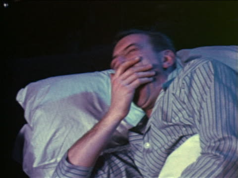 1957 man with pajamas in bed yawning + rubbing face / industrial