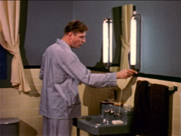 1957 man with pajamas in standing in bathroom looking in mirror + shaving with electric razor / indus. - 1957 stock videos & royalty-free footage