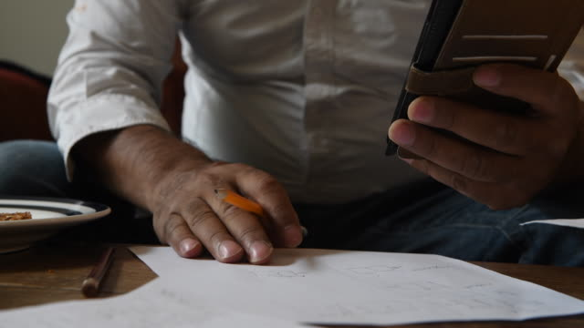 man with phone in hands making notes with a pencil - pencil isolated stock videos & royalty-free footage