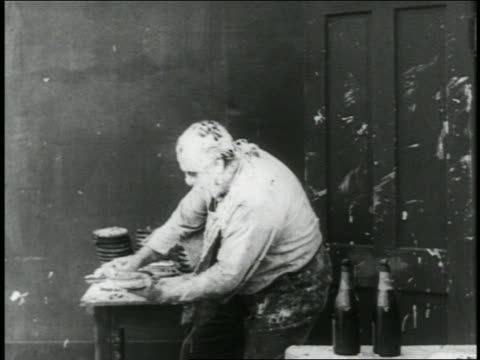b/w 1916 man (eric campbell) with pie on face picking up 3 pies / short - anno 1916 video stock e b–roll