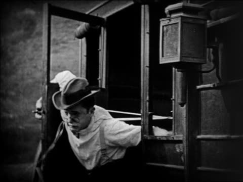 stockvideo's en b-roll-footage met b/w 1924 man with pincenez being held by suspenders in stagecoach holdup / feature - 1924