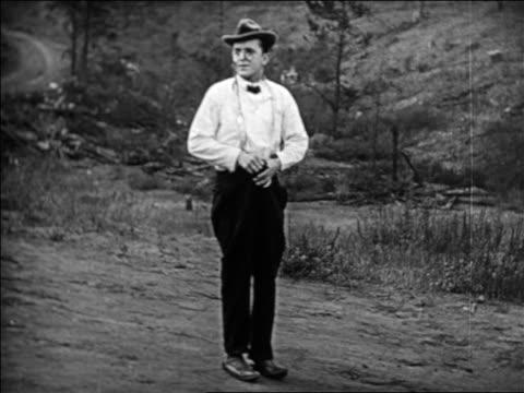 vidéos et rushes de man with pince-nez + falling down pants walking off screen / feature - 1924