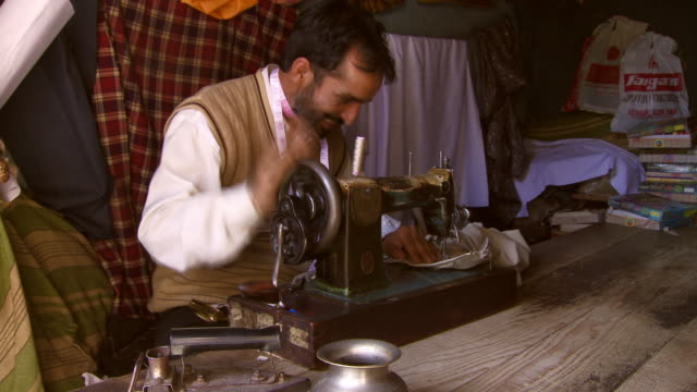 Man with pink measuring tape around his is sewing clothes on antique sewing machine