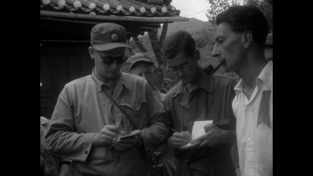 Man with pipe in mouth and ribbon pinned to shirt talking to US Marine journalists writing in notepads / MS man and journalists / MS man / man...