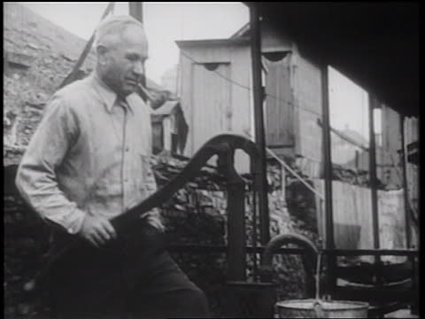 b/w 1939 man with pipe pumping water by shack outdoors / documentary - vattenpump bildbanksvideor och videomaterial från bakom kulisserna