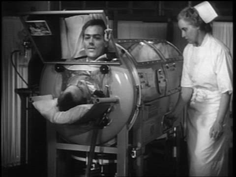 b/w 1948 man with polio in iron lung talking into mirror / nurse adjusts controls on iron lung - polio stock videos & royalty-free footage