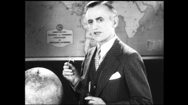 vídeos de stock e filmes b-roll de man with polished hair and suit speaking to the camera next to a globe and in front of a map, he holds up some wiring - 1940 1949