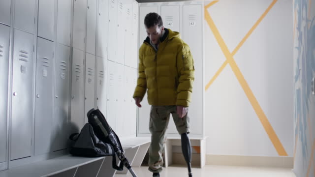 Man with prosthetic leg getting ready in changing room