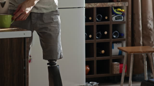 Man with prosthetic leg making hot tea