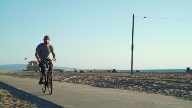 man with prosthetic leg riding a bike at the beach - artificial limb stock videos & royalty-free footage