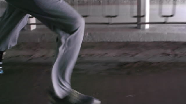 Man with prosthetic leg running under bridge