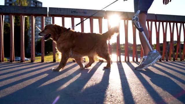 Man with prosthetic leg walking a dog