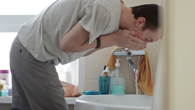 Man with prosthetic leg washing face in the morning