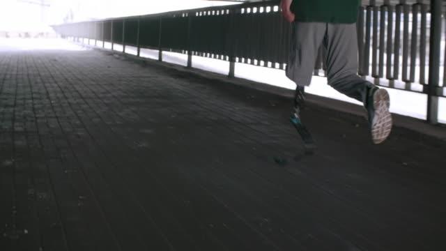 man with prosthetic running leg jogging under bridge - andersfähigkeiten stock-videos und b-roll-filmmaterial