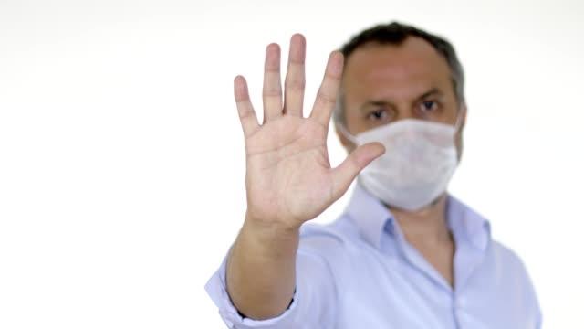 手のジェスチャーで停止を示す保護マスクを持つ男 - 断る点の映像素材/bロール