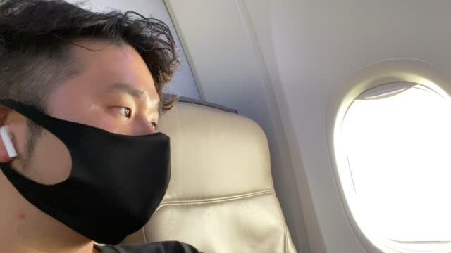 mann mit schutzmaske im flugzeug - gestrandet stock-videos und b-roll-filmmaterial