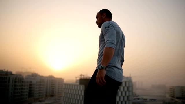 vídeos y material grabado en eventos de stock de hombre con los brazos levantados en la puesta del sol - tejado