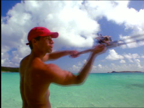 vidéos et rushes de rear view man with red cap standing in shallow ocean water casting fishing rod / virgin gorda - casquette de baseball