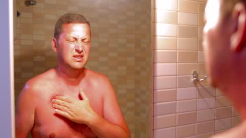 stockvideo's en b-roll-footage met man met rode, jeukende huid na zonnebrand - pellen