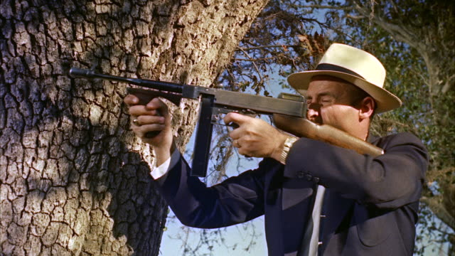 vídeos de stock e filmes b-roll de ms man with rifle in an orchard fires rifle - gânguester
