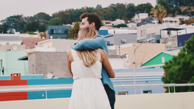 man with ring embracing girlfriend on rooftop - coppia di giovani video stock e b–roll