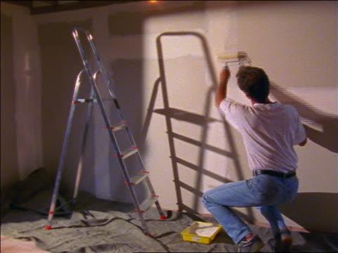 Man with roller kneeling + priming walls of house / France