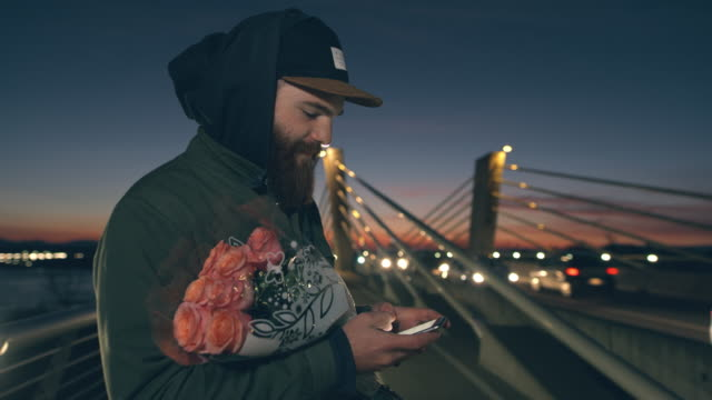 ms man with rose bouquet using smart phone on bridge at dusk - internet dating stock videos and b-roll footage