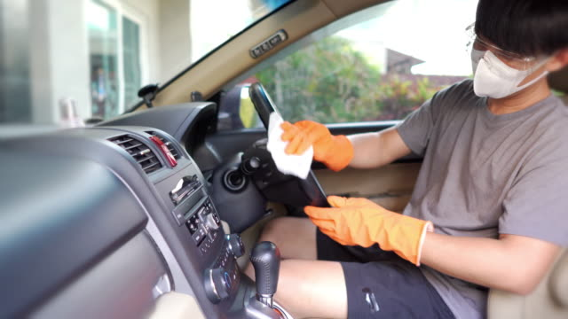 a man with safety glasses and face mask with hand glove wiping down on surfaces of car interior for cleaning covid-19 virus - dustman stock videos & royalty-free footage