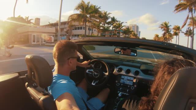 日当たりの良い通り、マイアミ、フロリダ州でコンバーチブルを運転する自分撮りスティックを持つmsの男 - マイアミビーチ点の映像素材/bロール