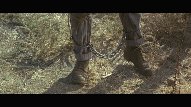 1967CU Man with shackled legs walking on weedy ground, low section
