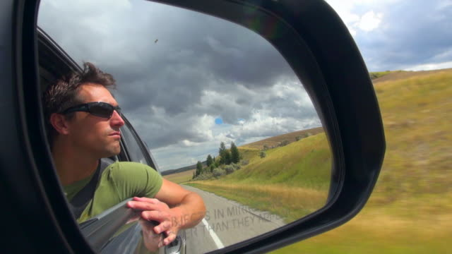 Man with Shades Shot on the Side Mirror of Vehicle Going to Idaho Falls