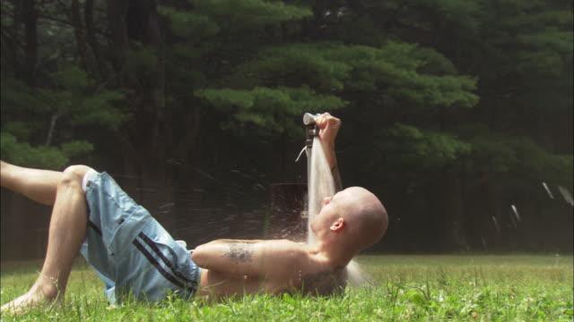 man with shaved head and tattoos lying under running faucet in park / squirting water from mouth / connecticut - badbyxor bildbanksvideor och videomaterial från bakom kulisserna