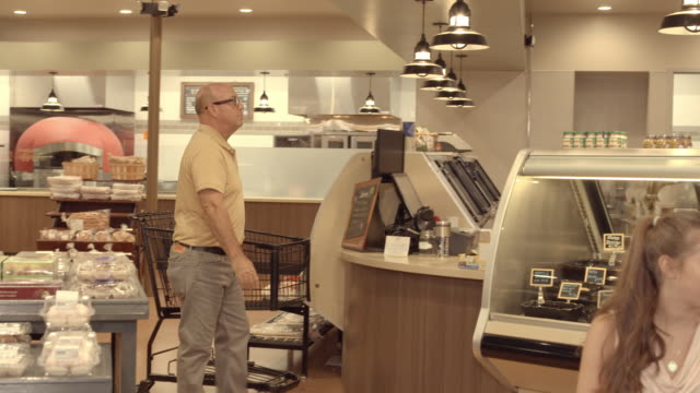 DS man with shopping cart approaches deli counter in supermarket