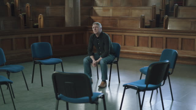 Man with silver hair sat in circle of empty chairs