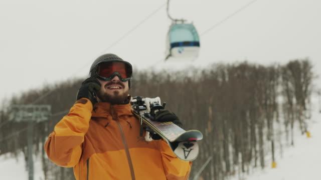 vídeos y material grabado en eventos de stock de hombre con monopatín hablando en el teléfono móvil 4k stock video... - chaqueta de esquiar