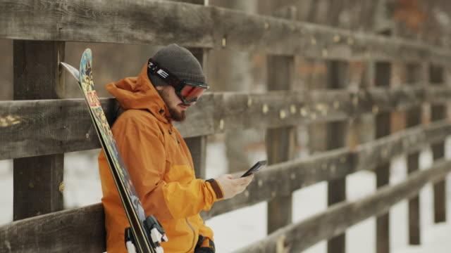 携帯電話4kストックビデオで話しているスキーを持つ男. - 受話器点の映像素材/bロール