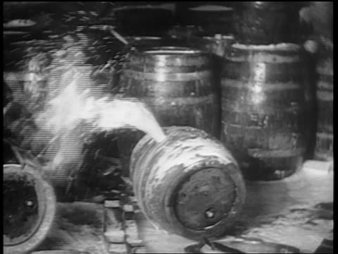 b/w 1932 man with sledgehammer hammering spraying barrel of beer / chicago - anno 1932 video stock e b–roll
