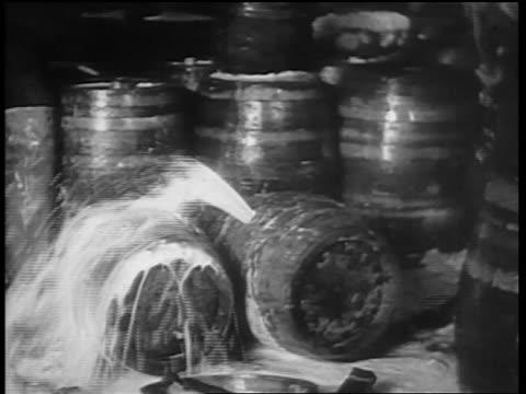 B/W 1932 man with sledgehammer hammering spraying barrel of beer / Chicago
