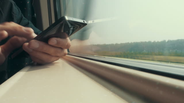 vidéos et rushes de man with smart phone in the train - téléphone mobile intelligent