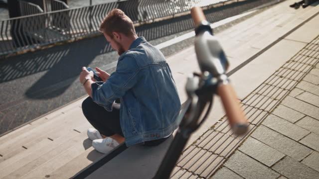 mann mit smartphone sitzt von elektroroller - casual clothing stock-videos und b-roll-filmmaterial