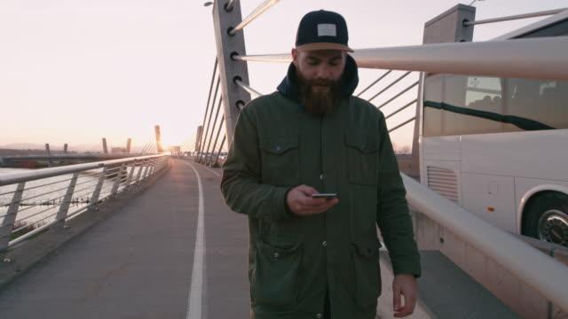 ms-mann mit ihrem smartphone zu fuß auf die brücke - blick nach unten stock-videos und b-roll-filmmaterial