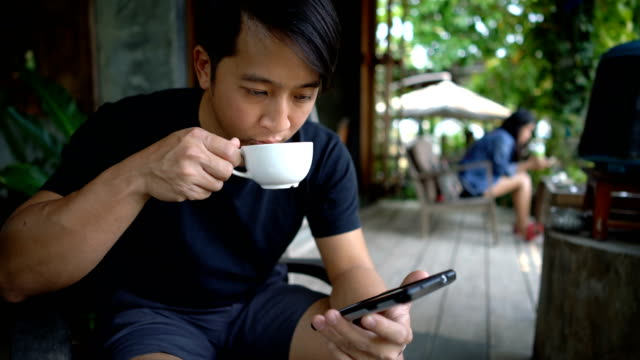 man with smartphone and coffee in coffee shop. - south east asian ethnicity stock videos & royalty-free footage