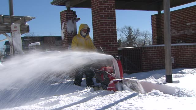 man with snow blower during the day on february 12 2012 in new york new york - fanghiglia video stock e b–roll