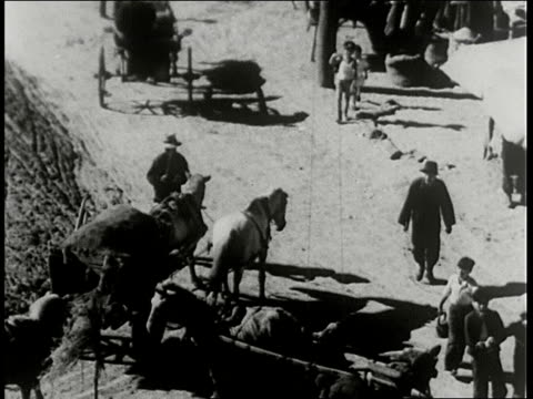 stockvideo's en b-roll-footage met man with son on shoulder hs chinese village ms chinese merchant reviews paper man bows / manchuria - 1938