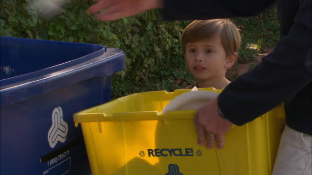 vídeos de stock e filmes b-roll de cu, man with son (4-5) throwing garbage into recyclable bin, los angeles, california, usa - lixeira