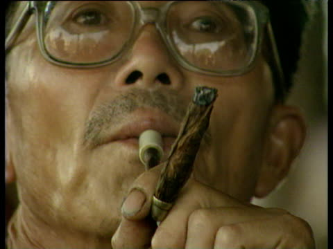 man with spectacles smoking cigarette through pipe chengdu china - nikotin stock-videos und b-roll-filmmaterial