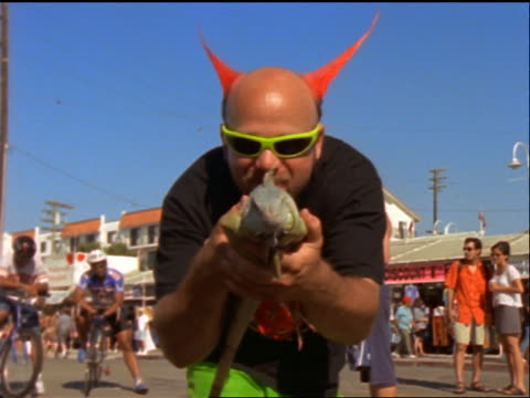 vídeos de stock e filmes b-roll de man with spiked dyed hair holding lizard towards camera / venice beach, ca - punk