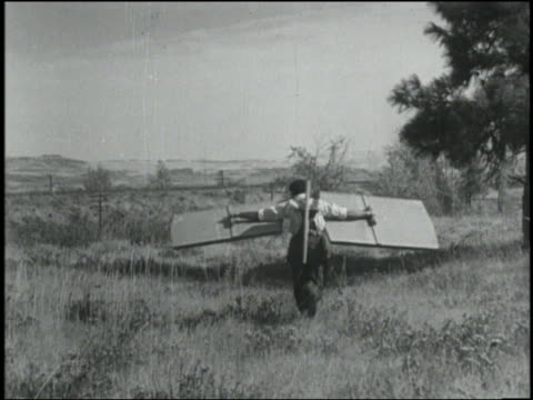1934 b/w man (hank fadis) with square wings on arms + tail on back running in field away from camera / rowena, oregon - air vehicle stock videos & royalty-free footage