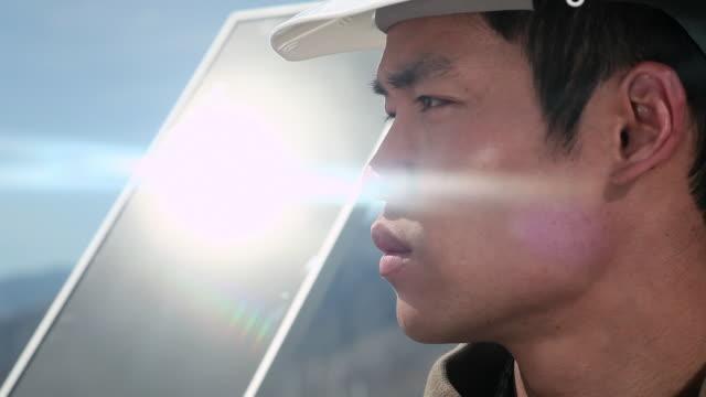 Man with sunlight reflecting off solar panel